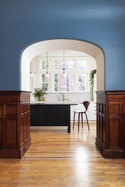 Dyer allocated the entry to the niche, saving and reinstalling the woodwork. It frames a beckoning view of the kitchen, as well as the striking new windows over the sink.