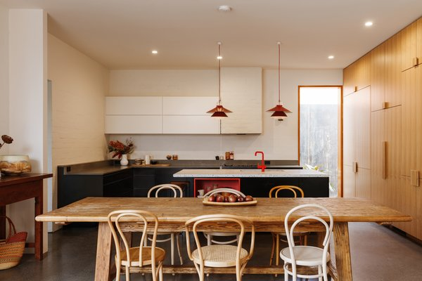 The stove was kept in place in order to retain the position of the gas and venting. The designer dropped the sill on the right-side window to the floor. Sleek black cabinetry is topped with Essastone Concrete Pezzato weathered stone on the perimeter, and custom terrazzo on the island.