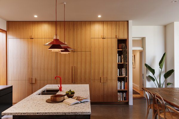 A wall of custom blackbutt cabinetry conceals the fridge and lots of storage.