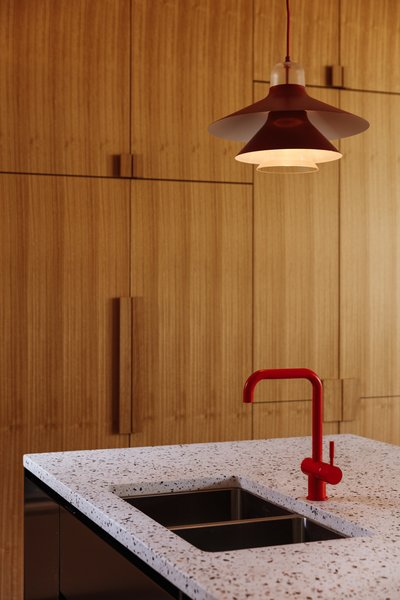 Pops of red—via the Louis Poulsen lights and Vola tap—are a nod to the homeowner's favorite hue.