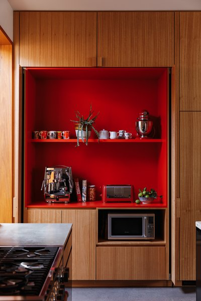Bright red laminate shelves hold the family's coffee supplies in a delightful reveal.