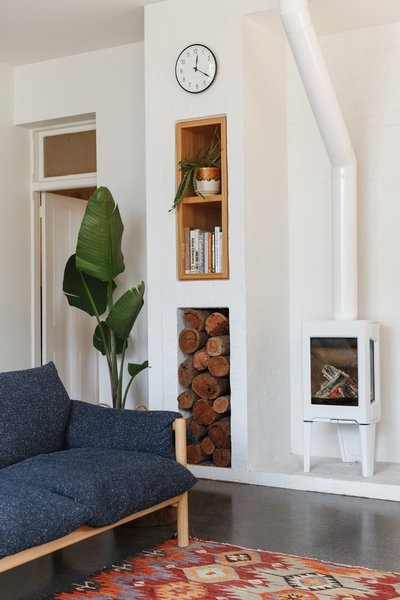 "An inset shelf is a decorative feature above the firewood storage. ""We enjoy the low sun in the winter mornings and the toasty warmth from the Jotul stove, which heats the whole back of the house,"" say the clients."