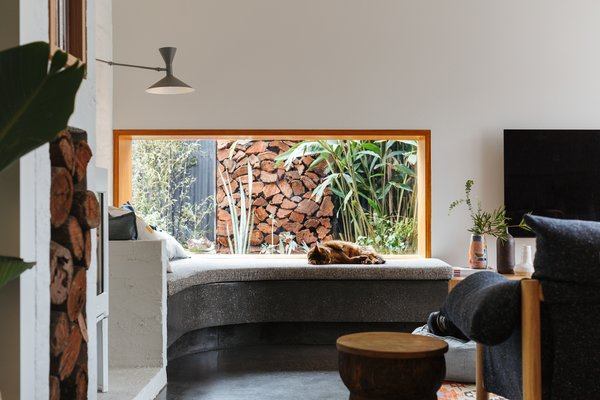"A picture window over a custom concrete bench fashions a window seat. ""Family, friends, and animals all enjoy the various places to relax in the lounge,"" says the homeowner. ""The window seat is universally the most prized nook in the home."""