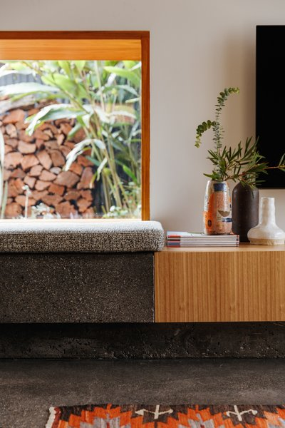 The concrete bench meets the wood of the built-in media cabinet. The floors are also concrete, poured to match the existing floors in the kitchen.