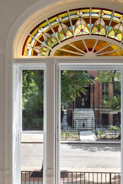 """The stained glass windows """"bring that little bit of sprinkling of color into the space, and then everything else is just super high-contrast white,"""" says Rausch."""