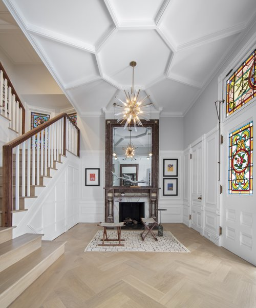 The team installed a more appropriately scaled staircase so that the foyer is a proper entry point to the house. The radial ceiling trim accents a new chandelier.