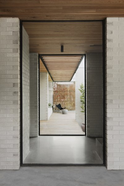 Glass panels in the hallway frame outdoor views and create an expansive sense of the property.
