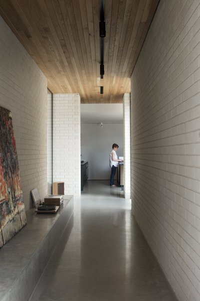 A view toward the living spaces in the pavilion, which includes the kitchen, dining room, and living room. The nine-foot-tall ceilings are clad in American oak, and the concrete plinth is intended for art display—but also works well for a record player. The floors are natural gray polished concrete slab with integrated hydronic heating.