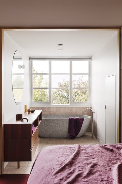 The adjoining bath is outfitted in tumbled pink stone tiles and a gray marble stone tub from Apaiser.