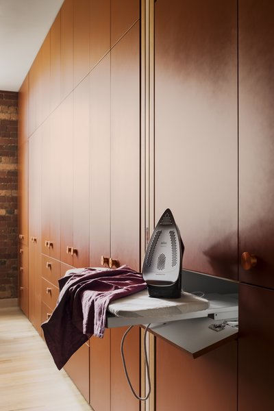 A pull-out ironing board is tucked into the cabinetry.