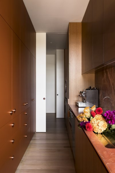 The corridor is 26 feet long and hosts a bar, sink, pantry, laundry, and drying room. Pocket doors allow the laundry to be closed off when needed.