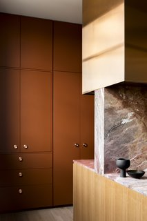 A view of the terra-cotta-colored utility corridor. The copper cabinet pulls are from Auhaus.