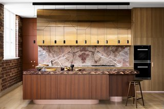 In the kitchen, a bank of copper-fronted cabinetry joins the pink marble backsplash. The island is set atop a curving pink base that gives it some lightness.