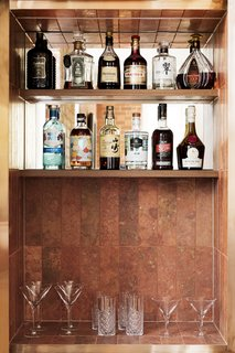 Rust-colored travertine tiles from Byzantine Design line a bar niche.