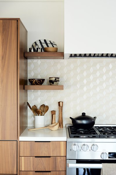 A Heath Ceramics tile backsplash in neutral tones offsets the custom walnut cabinetry.