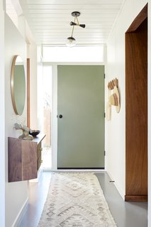 The firm swapped the door orientation and painted it sage green. They also preserved the surrounding lites to keep the natural light flowing inside. The original wall paneling on the right was painted a bright white, and new hooks corral coats.