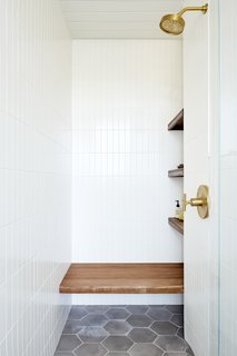 Floor tile from Cle runs inside the shower, where the niche and bench are fashioned from Tiger wood.