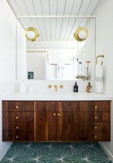 A custom mirror was fitted to the wall space above the bespoke floating vanity. Cedar & Moss sconces mounted over the mirror are sophisticated accents.