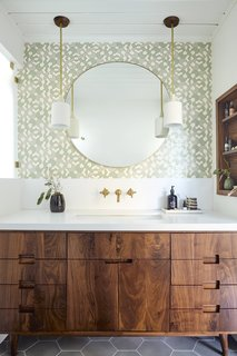 "A walnut vanity is topped with a Silestone White Zeus quartz counter. The pendant lights framing the mirror are from Cedar & Moss and the wallpaper is from Heath Ceramics + Hygge & West. ""We decided to add in some pops of color and pattern in the kids' bathroom with the bright tile, and then the master bathroom with that cool wallpaper,"" says Foken."