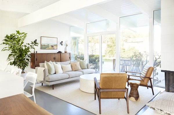 Removing the partition wall makes it so the entire living space benefits from the natural light that comes through the floor-to-ceiling glass in the living room, increasing the sense of indoor-outdoor flow throughout. A sofa from Article is joined by art from Lynne Millar for Juniper Print Shop and a vintage credenza.