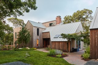 "The team removed the outdated exterior detailing and replaced it with vertical strips of Kebony Clear siding and a Freedom Gray copper standing seam metal roof. ""Kebony offered that same sort of silvery weathering that would get us that [Cape] aesthetic, and the feel of this house being set in the landscape,"" says Yoon."