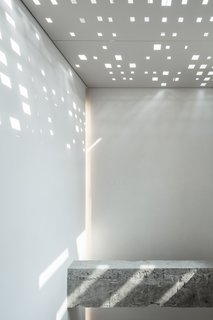 The play of natural light and texture from the structural beam becomes an art installation against white walls.