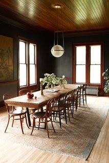 Walls painted Black Ink by Benjamin Moore set the tone in the dining room. The couple retained the original floors and beadboard ceilings, and left the woodwork as they found it. Nick built the table, which can seat 14, from a counter found in the barn, and the chandelier above it is from Rejuvenation.