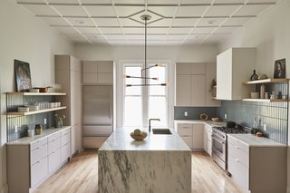 Now, the sizeable kitchen is an exceptional blend of old and new. The original floors, coffered ceiling, and windows are joined with IKEA cabinets with Semihandmade fronts, and Vermont-sourced Danby marble counters.