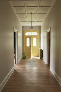 In the revitalized hallway, an IC Light S by Michael Anastassiades for Flos hangs over the front door, painted Benjamin Moore Yellow Highlighter.