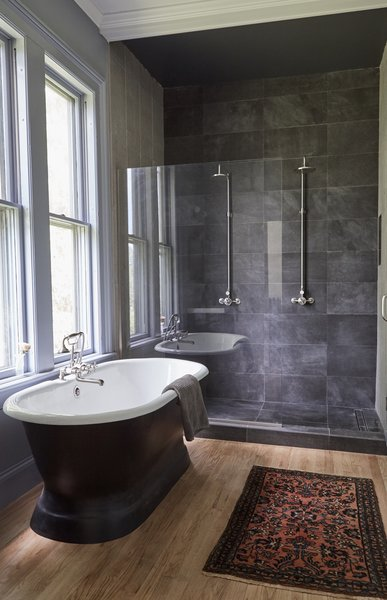 In a newly installed bathroom, slate tile encases the shower and a soaking tub takes in the view of a cluster of 100-year-old Norway Spruces.