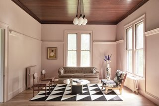 """The living room is dubbed the """"Ladies Who Lunch"""" room. Benjamin Moore's Chippendale Rosetone covers the walls, in rich contrast to the preserved wood ceiling, and a medley of vintage furnishings fills out the space. The rug is from IKEA and the chandelier is Schoolhouse Electric."""