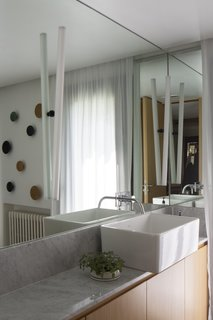 A Carrara marble counter lines the vanity, and a mirror stretches from wall to wall.