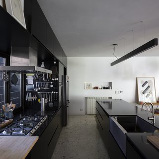 """The white terrazzo floor was made the """"old-school"""" way, in situ with large marble stones. The counters are Silestone Black Tebas."""