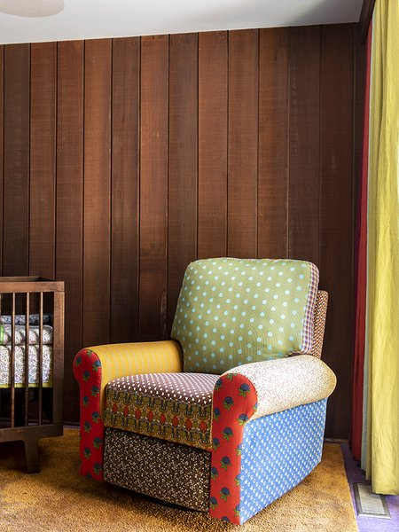 """""""Gliders are all pretty ugly—even the ones that are sort of trying to not be,"""" says Merrill. """"So, we decided to get the biggest and clunkiest–just the most basic, giant thing–and turn it into something fun."""" The chair is upholstered in a quilt-like manner using fabric the homeowner collected."""