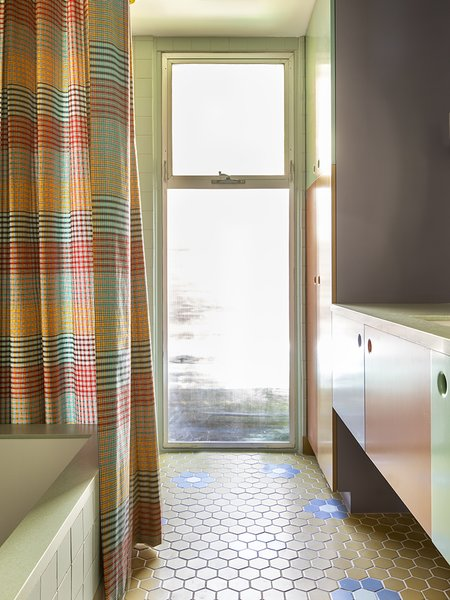 """The new color palette combines a medley of hues, including mustard, mint, rusty orange, and lavender. The bathroom floor, tiled with oversized flowers, is paired with a plaid shower curtain. The client encouraged the firm to stretch here: """"I think we originally had something with a bit less color, but she was always pushing us,"""" says Merrill. """"It was so fun."""""""