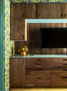 """A custom built-in with laminate accents in the dressing area is also by Joshua West Smith. """"He did such a beautiful job of making cabinetry that looks like what could have been in the house,"""" says Merrill."""