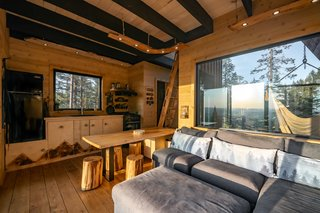 Dignard fitted out the interior with a medley of woods—cedar, larch, and aspen—and added shou sugi ban accents, such as the mountain scene running across the kitchen cabinets. The couch folds out for an extra bed.