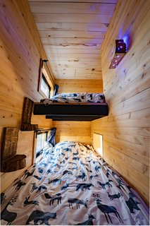 """The bunk room is L-shaped and has two single beds. Each bed has an exterior window, as well as an interior window that looks into the house. """"So, at night we can all say, 'Goodnight,'"""" explains Dignard."""