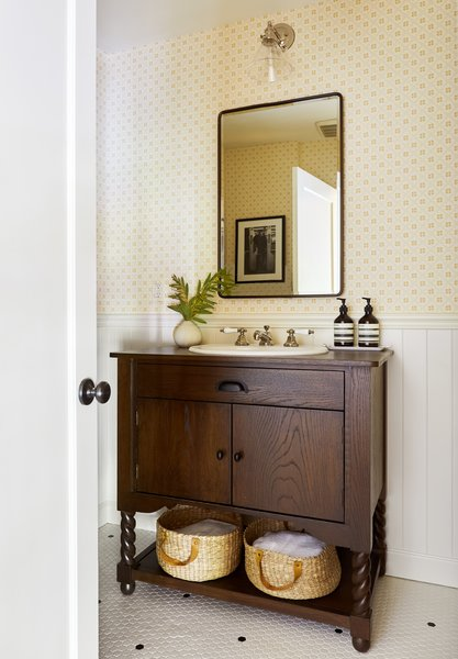 Small-scale hex floor tiles work better with the home's vintage—as does the new wainscot and Swedish reproduction wallpaper found at Walnut Wallpaper in Los Angeles. When Zachary couldn't find the perfect antique for the vanity, the designer had one custom built.