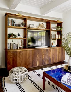 Zachary's father—a fine woodworker and production designer for television—built the walnut unit. The beadboard backing brings texture to the display and syncs with other applications in the house.