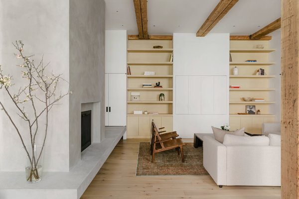 Floor-to-ceiling shelves and storage bookend a cabinet that conceals the television.