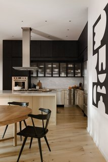 The stainless-steel elements, including the counter and cabinets, were also kept in place for their industrial character. The island was reworked and topped with marble.