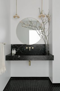 The showpiece in the new bathroom is the floating vanity with an integrated sink carved from a block of Nero Marquina marble.
