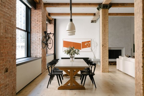 Bleached walnut replaced cold concrete floors in this family-friendly renovation of a dated loft in West Chelsea's late 19th-century Spears Building. To make the loft feel more welcoming, architects Ravi Raj and Evan Watts toned down the heavy industrial elements of the 2,700-square-foot loft with a warmer and lighter palette and added custom built-ins for a streamlined look. At the same time, the loft still preserves much of its historic appeal—from the exposed brick seen throughout the home to the oversized openings left intact.