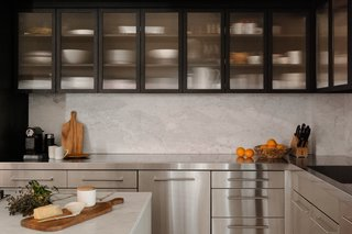 Marble covers the backsplash, and new upper cabinets inset with fluted glass were added.