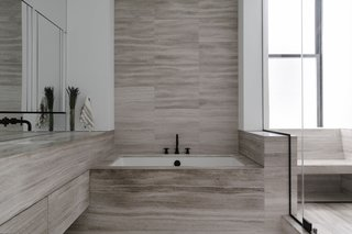 The bathroom layout was reconfigured for more privacy, and wrapped in honed beige marble.