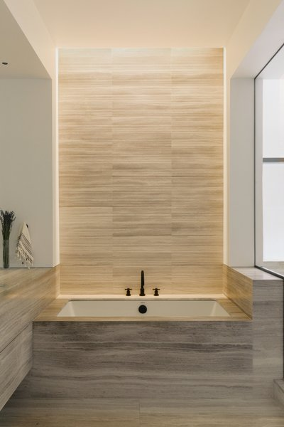 "The tub backdrop is composed of bamboo-cut textured marble tile. ""When the lights are on, it casts a really beautiful waterfall effect of light across the texture,"" says Watts."