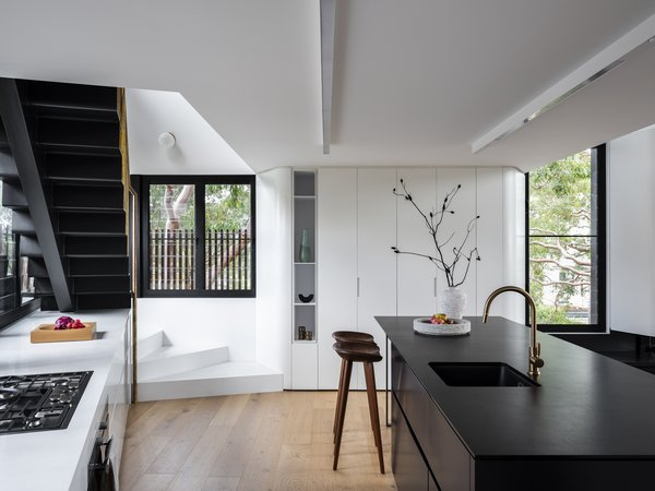 The kitchen's Caesarstone Pure White countertop extends to the winding tread at the base of the stairs leading up to the mezzanine. Black granite covers the island.