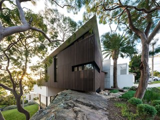 """Spotted gum slats screen the interior from the street, while allowing light to pass through and occupants to look out. """"The vertical battens mimic the rhythm of the trees. A sharp-edged roof accent highlights the sensibility to the rock below, and draws the eye up to the tree canopy, [both] internally and externally,"""" says Litera."""