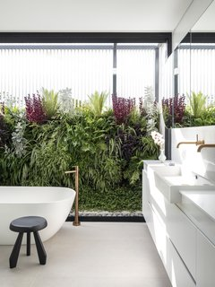 Despite facing the street, the master bathroom contains a delightful surprise: a private outdoor shower with a green wall.